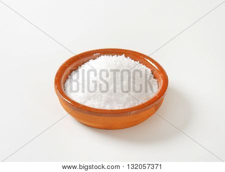 bowl of coarse grained salt on white background