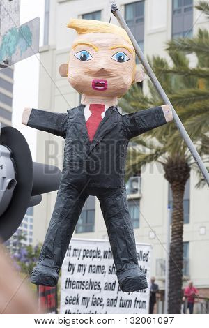 SAN DIEGO USA - MAY 27 2016: A pinata made in the likeness of Donald Trump hangs from a long pole at a protest outside a Trump rally in San Diego.