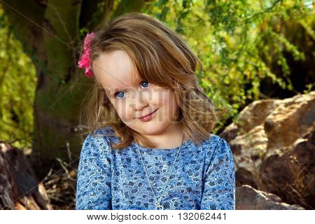 A very cute little girl sits under a mesquite tree and looks off camera with an