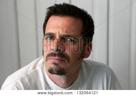 A man with a goatee scowls at the camera. He looks upset.