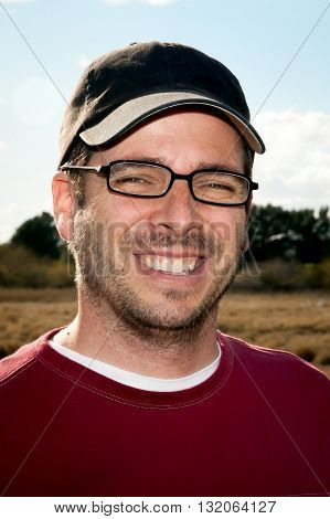 Handsome man looking a bit goofy with facial stubble reading glasses and a baseball cap.