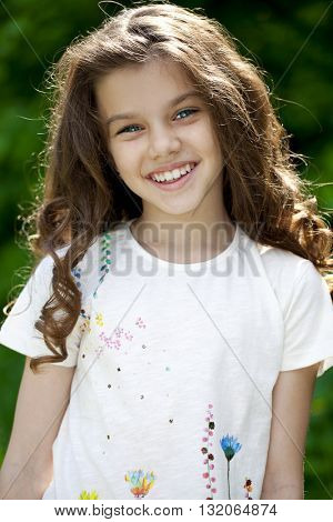Portrait of a beautiful young little girl on the background of summer park