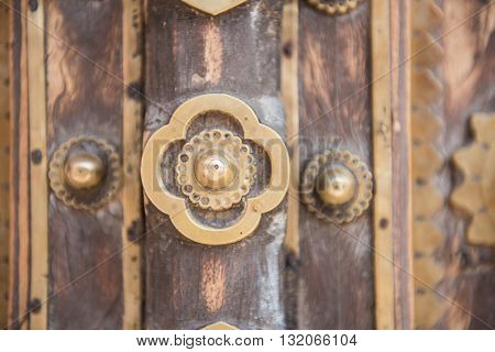 Wonderfully decorated wooden door in Chandra Mahal of City Palace at Jaipur. Iron decorations along with forged iron doorknocker rings of golden color are seen.