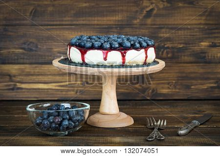 Cheesecake with blueberry and jam on wooden background in rustic style