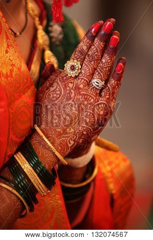 Folded henna decorated hands of an Indian bride during a prayer in a traditional Indian wedding