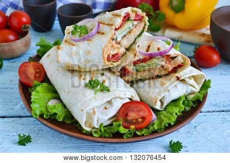 shawarma Lavash with chicken tomatoes lettuce and peppers on a blue background