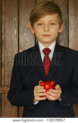 Boy in a suit with a red piggy bank - business concept