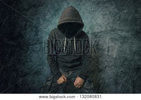 Spooky evil criminal person with hooded jacket standing in rain in front of concrete wall.