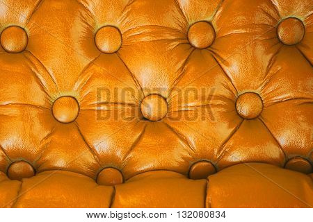 Texture of vintage golden yellow leather upholstery with buttons retro furniture background