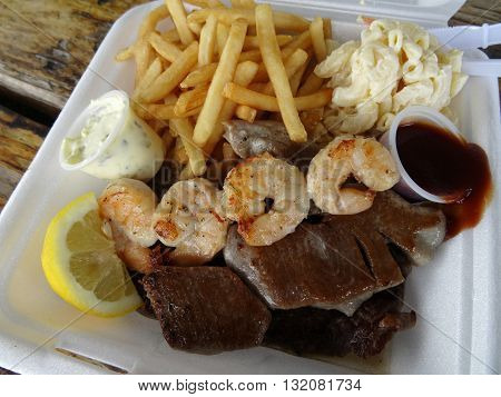 Mix Plate Dish of Shrimp Grilled Ahi Steak french fries macaroni salad lemon slice small cups of steak and tartar sauce in a styrofoam plate with plastic knife and fork on a wooden table.