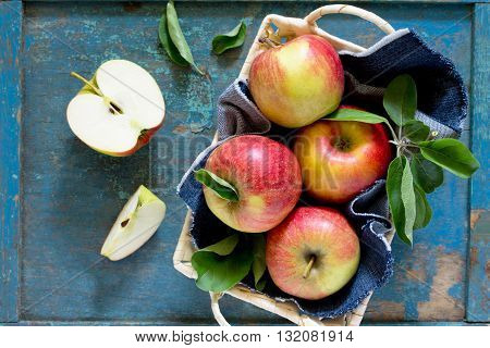 Harvest Fresh Organic Red Apples In A Wicker Basket On A Rustic Wooden Table, Top View With Copy Spa