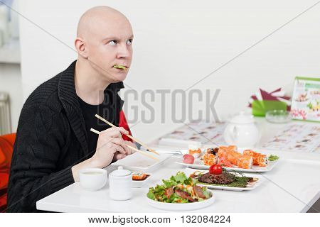 Young man is sitting at sushi bar, and having a lunch of japanese kitchen