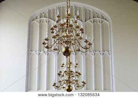 large Brass candelabra inside english church with white background