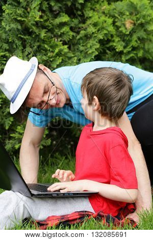 father and son  playing on the computer (laptop) in a park