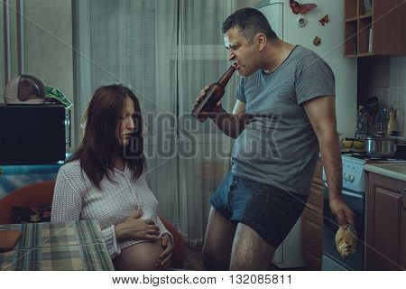 Kitchen sits sad and depressed woman near a drunken husband. Social problems of the family.