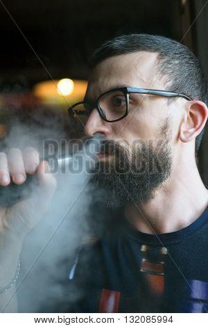 Bearded Smoking Vaporizer And Blows Smoke