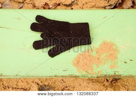 Lost Woolen Gloves On Green Bench. Sandy Gren Wooden Bench.  Sandbox With Dirty Sand In Kindergarden