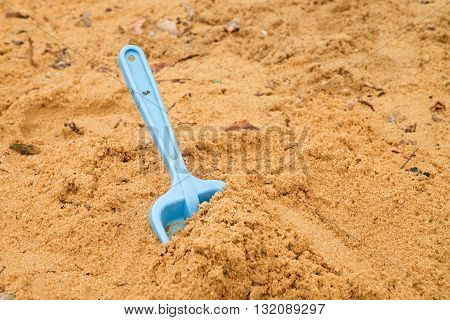 Blue Children Shovel Toy On White Sand, Plastic Play For Game. Mound Of Sand In Kindergarden.