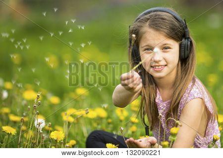 Little cute girl in headphones sitting in a field of dandelions.