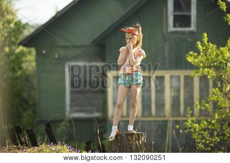 Little cute girl standing on a stump near a country house.