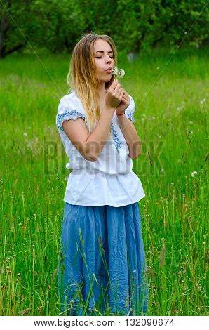 Sad young woman blowing on a dandelion in the hands