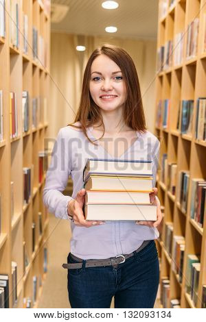 Attractive young female student with a stack of books in his hands between library shelves
