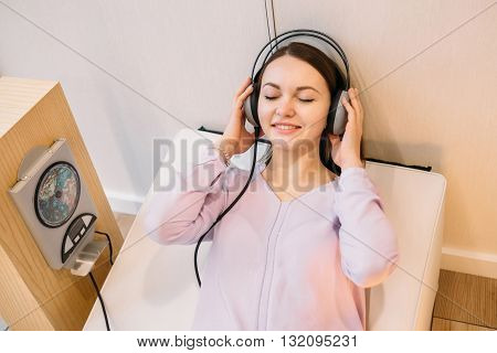 Girl listening to music lying on the sofa through the stereo system