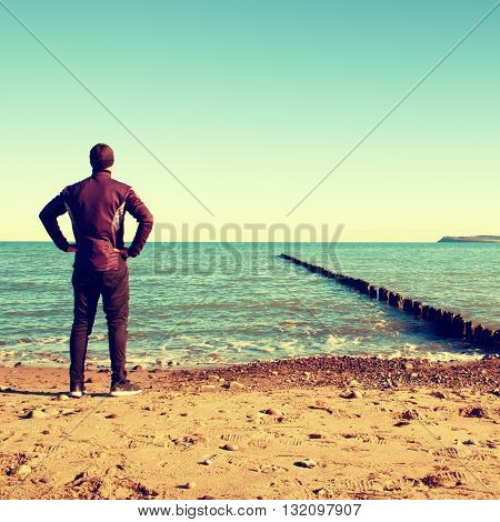 Tall Man In Black Suit Exercising And Make Stretching On Stony Beach At Breakwater.