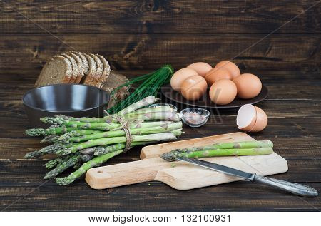 Still life with green asparagus and eggs on wooden background