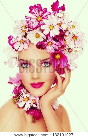 Young beautiful sexy girl with stylish make-up and colorful flowers around her face, on white background