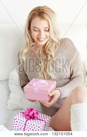 holidays, birthday, morning and people concept - happy young woman gift boxes or presents in bed at home bedroom