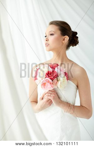 beauty, jewelry, people and luxury concept - beautiful asian woman or bride in white dress with peony flower, golden ring and bracelet