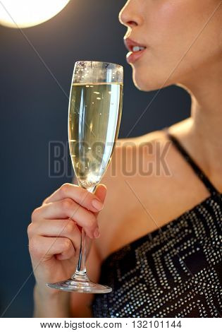 holidays, nightlife, drinks, people and luxury concept - close up of beautiful young asian woman drinking champagne at party over black background and spotlights