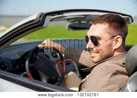 road trip, travel, transport, leisure and people concept - happy man driving cabriolet car outdoors