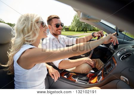 road trip, travel, summer vacation, technology and people concept - happy man and woman driving car and using gps navigator in cabriolet car