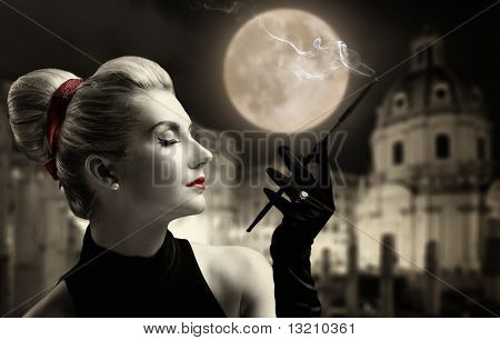 Beautiful young lady smoking. Old city behind her.