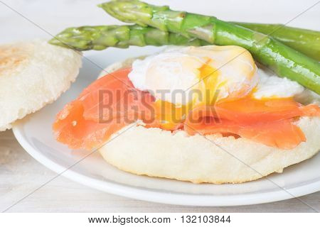 Close up of toasted English muffin with poached egg, flowing out yolk, salmon and asparagus