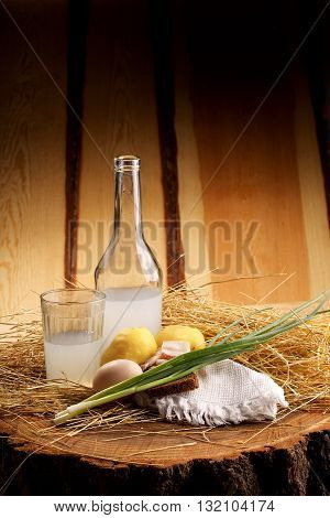 On A Stump In The Hay Is Moonshine Bottle, Bread With Lard, Potatoes And Egg