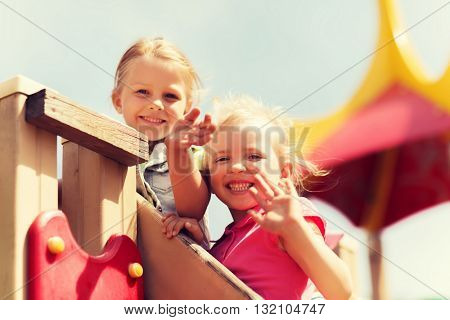 summer, childhood, leisure, friendship and people concept - happy little girls waving hands on children playground climbing frame