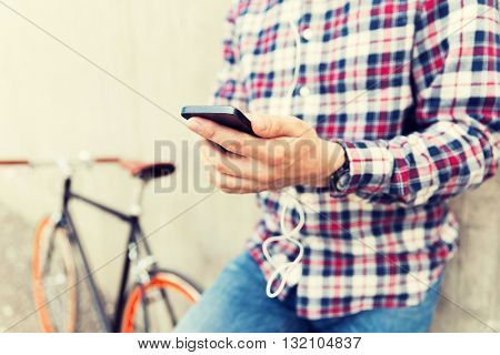 people, technology, leisure and lifestyle - close up of young hipster man in earphones with fixed gear bike listening to music on city street