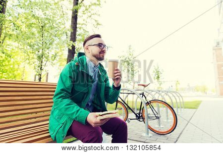 people, style, leisure and lifestyle - happy young hipster man with sandwich, coffee cup and fixed gear bike parked on city street