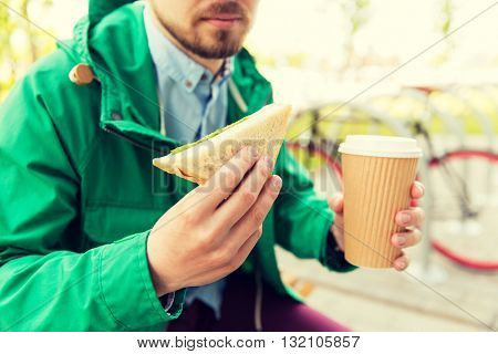 people, junk food, eating and lifestyle - close up of young man with coffee cup and sandwich eating and drinking on city street
