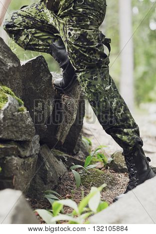 war, hiking, army and people concept - close up of soldier legs climbing on rocks in forest