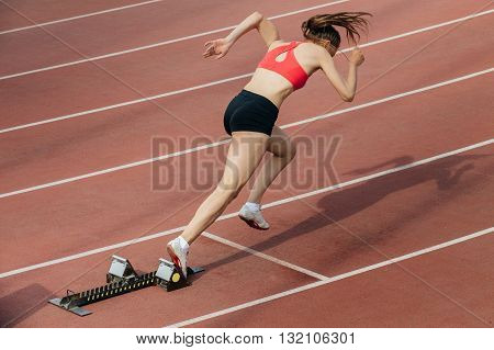 woman sprinter at start of 400 metres at stadium