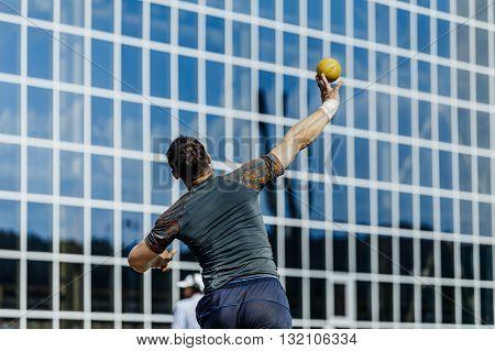 man athlete shot put at competition in stadium