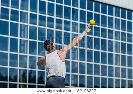 man athlete shot put at competition from back