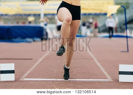 girl athlete of long jump. only foot jump from wooden board