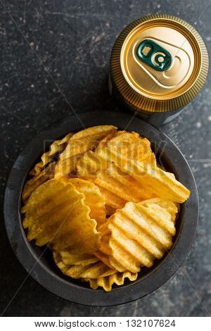 Crinkle cut potato chips on table. Tasty spicy potato chips with beer.