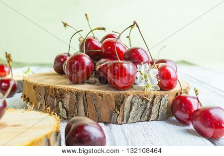 Red cherries heap merry on wooden rustic plate