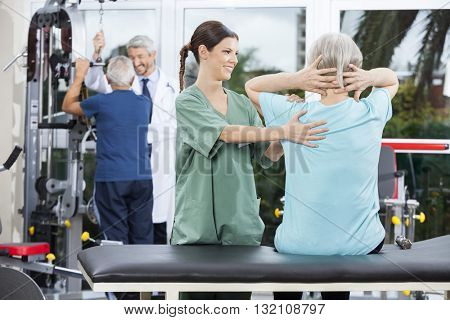 Nurse Assisting Senior Woman In Back Exercise In Rehab Center